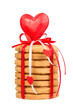stack of honey cake decorated with red ribbon and heart