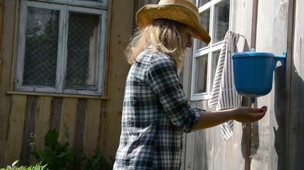 gardener girl woman wash hands under rural plastic washer tool