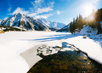Big Almaty lake on december. Water, ice, mountains and snow.