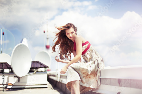 Beautiful woman in elegant dress on the top of modern building