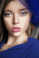 Portrait of elegant woman with blue hat in navy dress