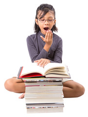 Young Malay Asian girl yawning in front of a pile of books