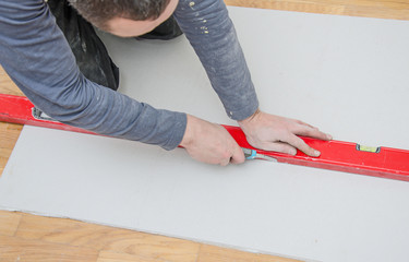 Man measuring and cutting gypsum plasterboard