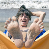 woman's toes relaxing on the beach
