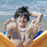 sandy  woman toes  moving and relaxing on the beach