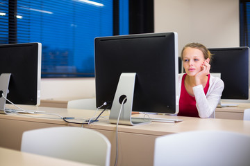 Pretty, young female college student using a desktop computer