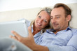 Couple in couch websurfing on the net with pad
