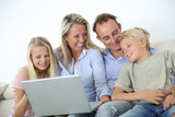 Family connected on internet with laptop