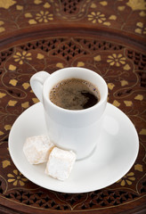 Cup of black turkish coffee on the vintage wooden table.