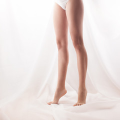 Woman's legs standing on tiptoe. high key