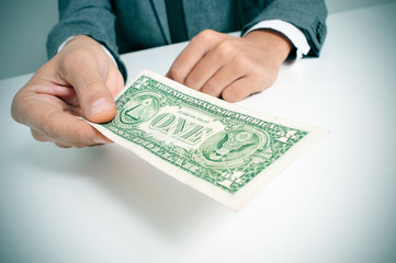 man in suit offering a one US dollar bill