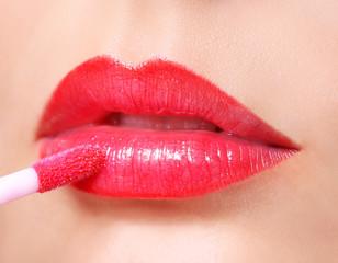 Red Lipstick. Lip Gloss on Sexy Lips and Brush. Makeup.