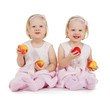two identical twin girls playing with apples