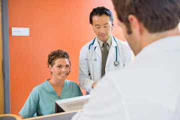 Nurse Looking At Patient With Doctor Standing By In Hospital