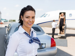Beautiful Stewardess Standing Against Limousine And Private Jet