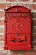 vintage red metal mail box on a brick wall
