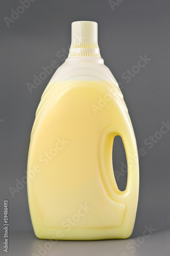 Transparent detergent plastic bottle isolated on gray