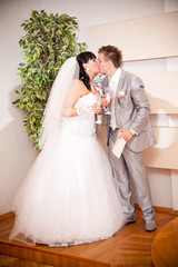 portrait of newly married couple kissing at wedding office