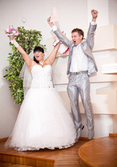 Happy newly married couple jumping up high at wedding office