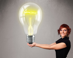 Beautiful lady holding realistic 3d light bulb