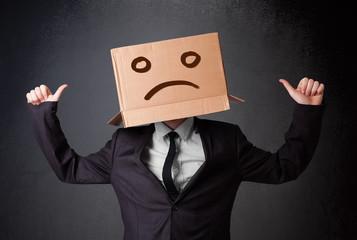 Businessman gesturing with cardboard box on his head with sad fa
