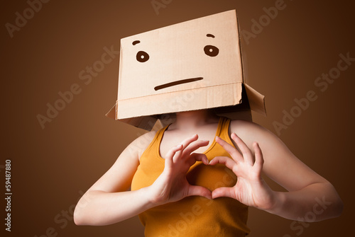Young girl gesturing with a cardboard box on her head with strai