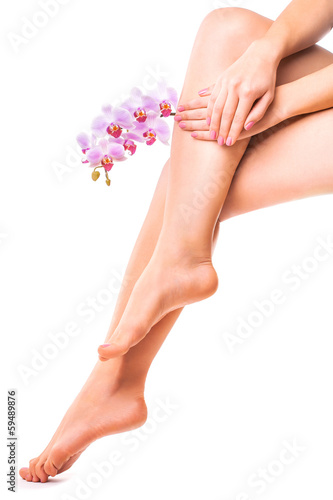 female legs and pink manicure with orchid flower