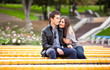 Beautiful dating couple hugging on yellow bench at park