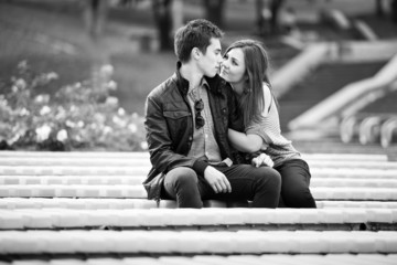 Monochrome photo of young couple in love kissing on bench