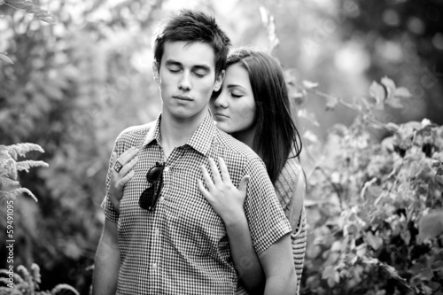 portrait of young couple hugging with closed eyes at park