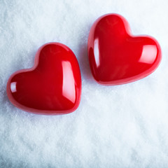 Two red glossy hearts on a frosty white snow background.  Love a