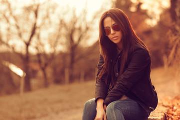 Beautiful female model at sunset. Wearing sunglasses. Outdoor po