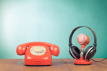 Retro red microphone, headphones and telephone on table