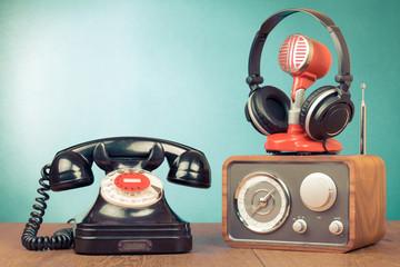 Retro rotary telephone, radio, headphones, microphone on table