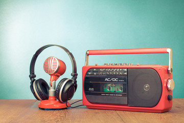 Retro red radio cassette player, microphone, headphones on table
