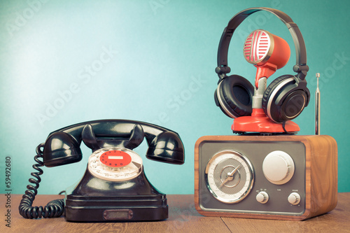 Retro rotary telephone, radio, headphones, microphone on table