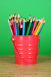 Colorful pencils in pail on table on green background