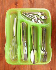 Green plastic cutlery tray with checked cutlery on wooden table