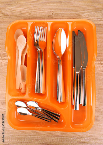 Orange plastic cutlery tray with checked cutlery and wooden