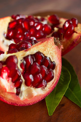 Ripe pomegranate with leaves on a wooden board.