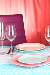 Table serving with colorful tableware on room background