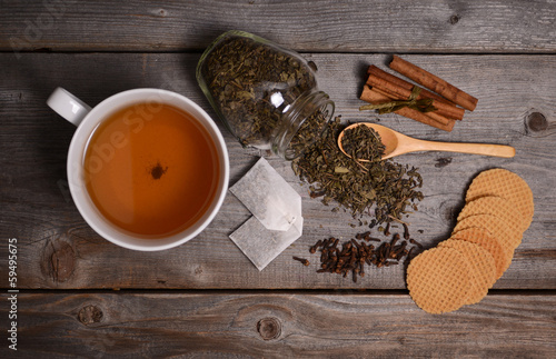 Cup of green tea, cinnamon and cookies on wooden background