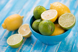Limes and lemons over blue wooden background