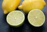 Sliced lime and whole lemons, black wooden background