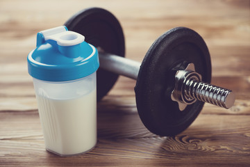Protein shake and a dumbbell on a wooden surface