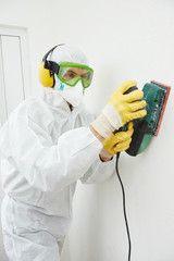 worker with sander at wall filling