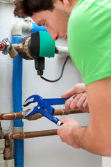 Handsome handyman turning off valves