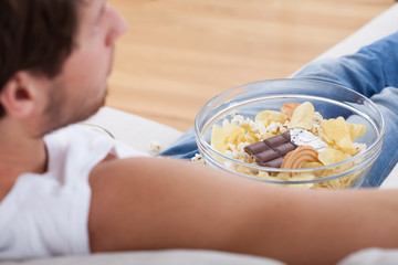 Man on couch with bowl full food