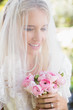 Smiling bride wearing veil over face holding bouquet