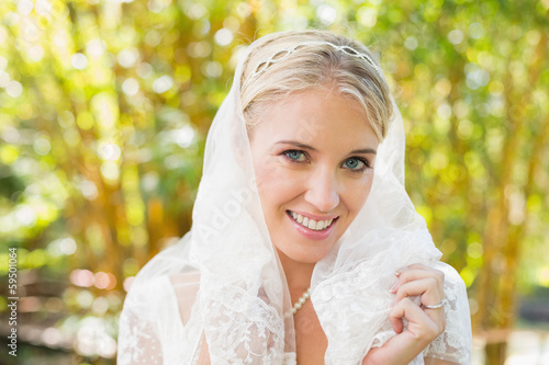 Beautiful blonde bride holding her veil smiling at camera © lightwavemedia